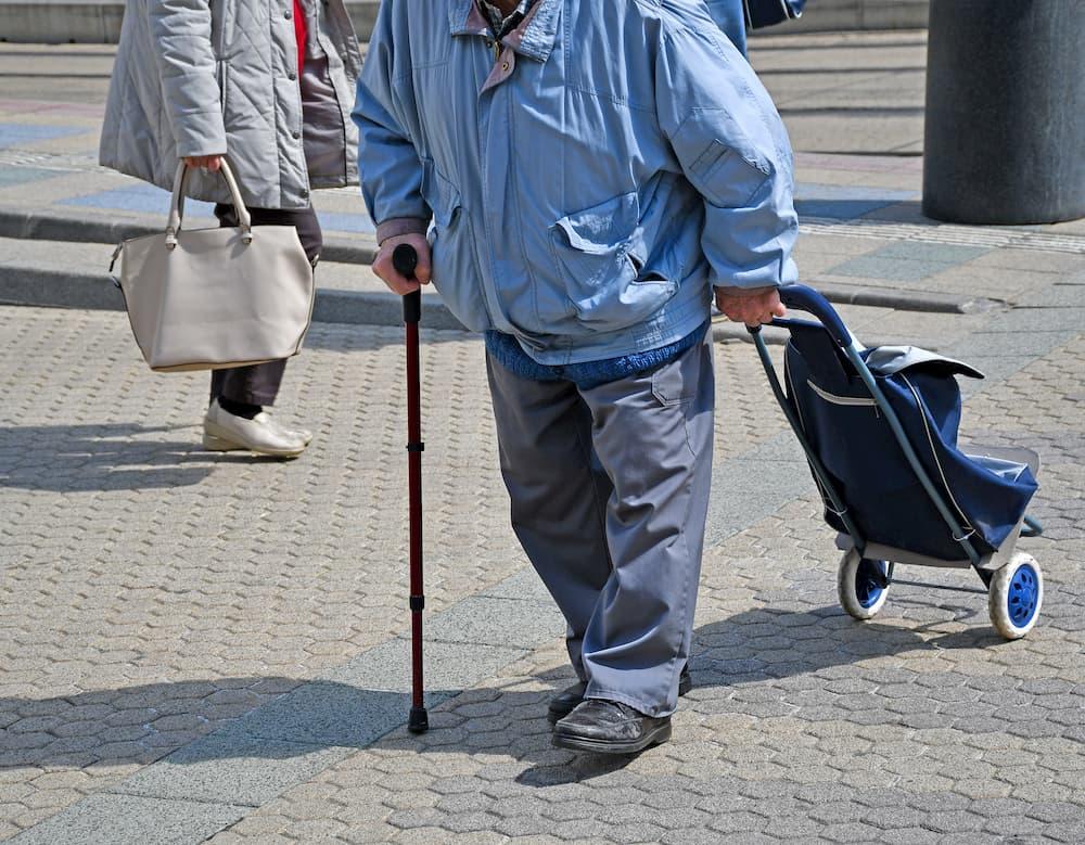 Alter Mann schiebt Einkaufstrolley © majorosl66, stock.adobe.com