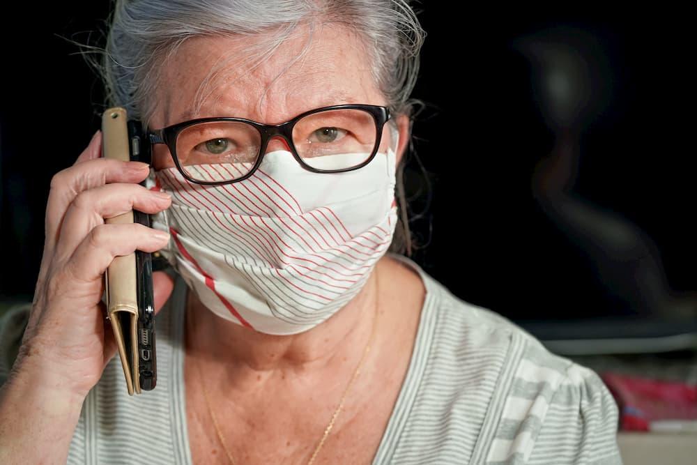 Seniorin telefoniert mit Maske © Lubo Ivanko, stock.adobe.com