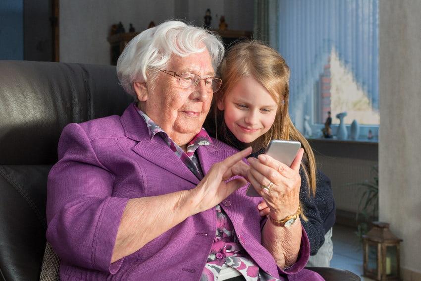 Großmutter, die ihrem Enkelkind etwas auf ihrem Smartphone zeigt © Markus Wegmann, stock.adobe.com